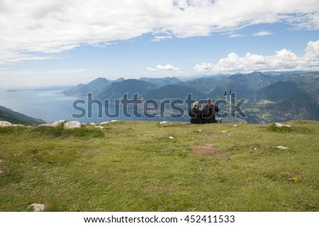 A couple resting on top of mount Baldo North Italy - stock photo