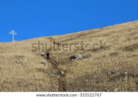A couple rising on a track to a lonely silver cross on the autumn mountain against a blue sky - stock photo