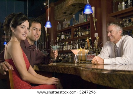 A couple sits at a bar while a bartender serves them - stock photo