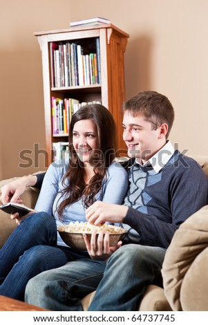 A couple sitting on sofa and watching television - stock photo