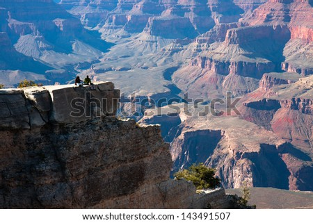 A couple sitting on the edge of a ravine. - stock photo