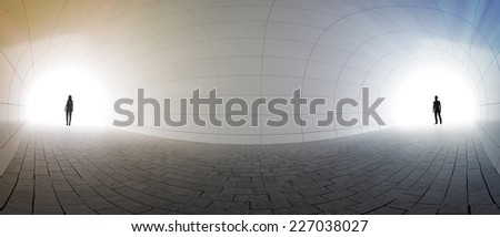 A couple standing at two ends of a tunnel - stock photo