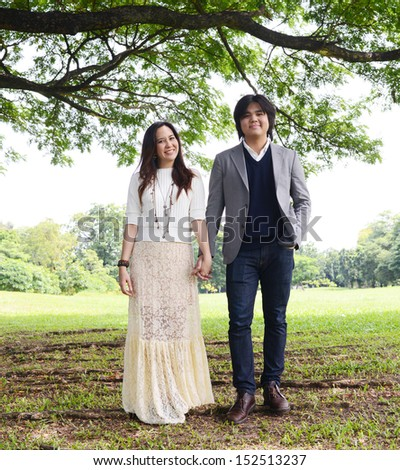 a couple standing under the rain tree - stock photo