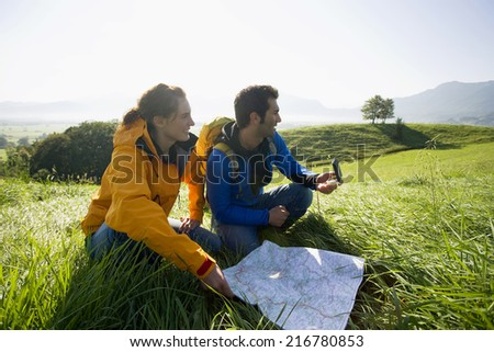A couple using a map and a compass to find directions. - stock photo