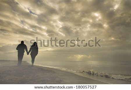 A couple walking along a misty beach, holding hands./ Couple on a cloudy beach - stock photo