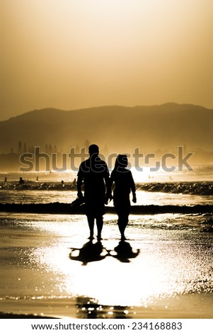 A couple walking at the beach of Byron Bay, Australia at sunset - stock photo