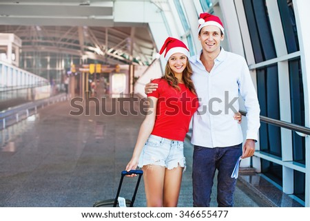 A couple wearing santa's hats departing to celebrate christmas abroad - stock photo