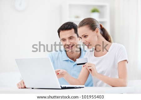 A couple with a credit card and a laptop at home - stock photo