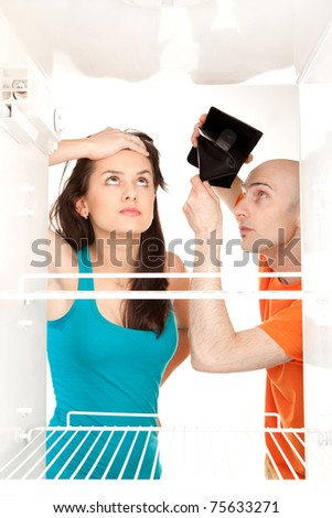 A couple with no money searching for food in an empty refrigerator whilst the man holds his empty wallet. - stock photo