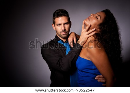 a couple with the man in a dominating position taking control in a sexy way - stock photo