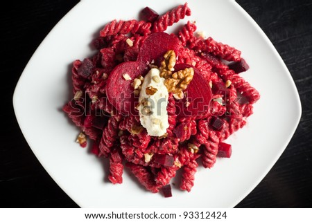 a course of pasta with red beets a dollop of gorgonzola cheese and a sprinkle of crushed walnuts on top. Served on a white dish over a black table - stock photo