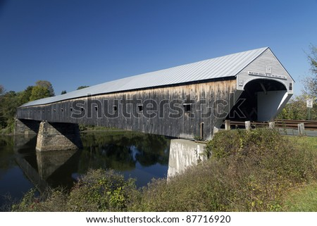 A covered bridge over a river - stock photo