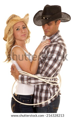 A cowboy and cowgirl tired up with a rope, getting close. - stock photo