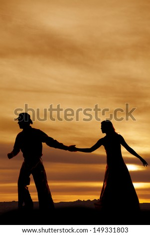 A cowboy and woman in the sunset holding hands. - stock photo