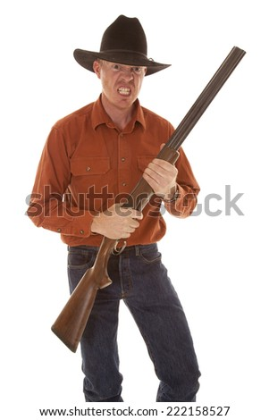 A cowboy holding on to a shotgun with a look of anger. - stock photo