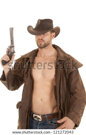 A cowboy holding up his gun with a serious expression on his face. - stock photo