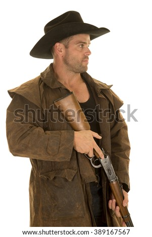 A cowboy in his duster holding on to his rifle looking serious. - stock photo