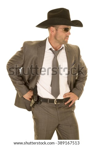 A cowboy in his suit and hat showing off his pistol on his hip. - stock photo