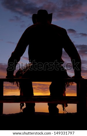 A cowboy in the sunset sitting on a fence. - stock photo