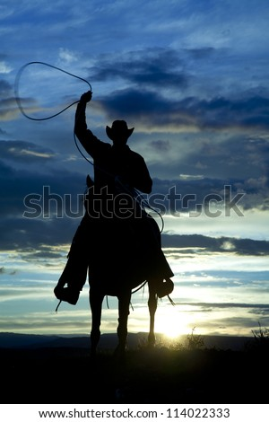 A cowboy is riding forward in the sunset with a rope above his head. - stock photo