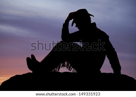 A cowboy is sitting and holding his hat. - stock photo