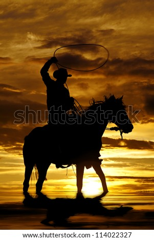A cowboy is sitting on his horse in the sunset and swinging a rope standing in water. - stock photo