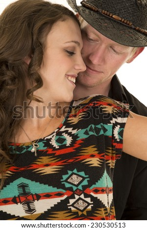 a cowboy looking down at his woman while she smiles. - stock photo