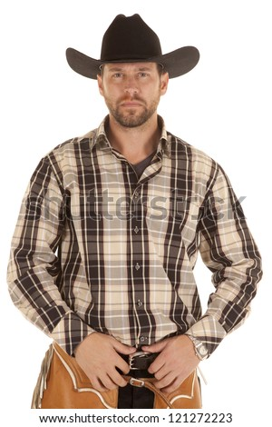 A cowboy with a serious expression holding onto his belt - stock photo
