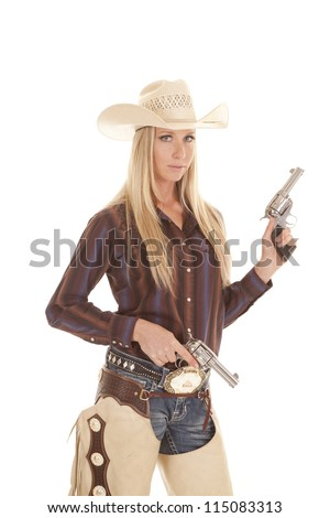 A cowgirl in her chaps holding on to her two pistols with a serious expression. - stock photo