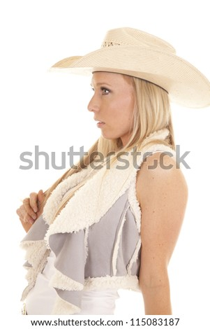 A cowgirl in her cream colored straw hat looking to the side with a serious expression on her face. - stock photo
