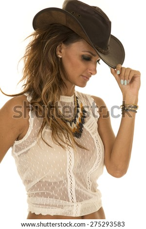 a cowgirl in her western hat, pulling down the brim. - stock photo
