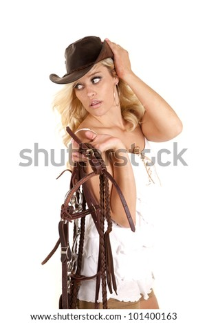 A cowgirl is holding a bridle and looking back over her shoulder. - stock photo