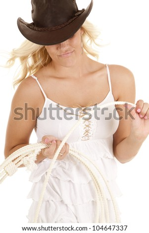 A cowgirl is looking down at a rope she is holding. - stock photo