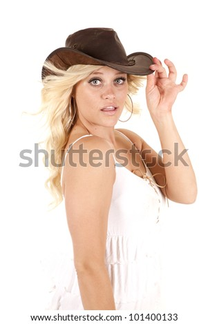 A cowgirl is standing with on hand on her cowboy hat. - stock photo