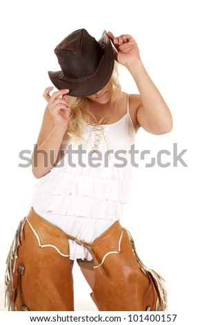 A cowgirl is wearing chaps and holding onto her hat. - stock photo