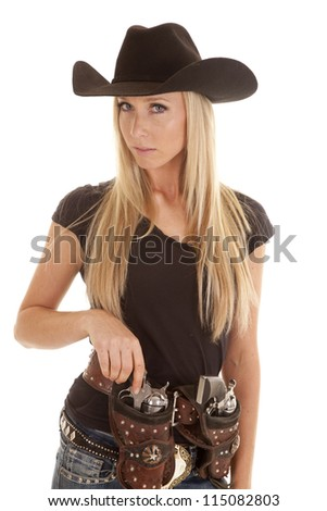A cowgirl placing one of her pistols in her holster with a serious expression on her face. - stock photo