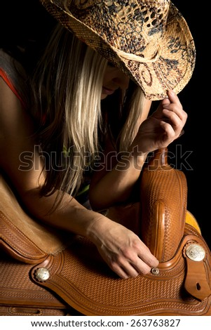 A cowgirl pulling her hat down, leaning on a saddle. - stock photo