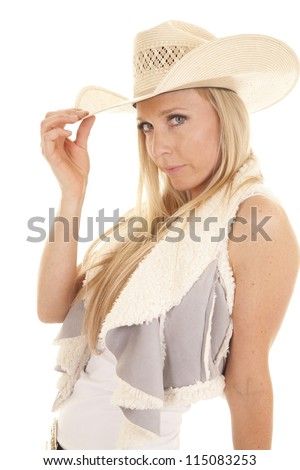 A cowgirl touching the brim of her hat looking at the camera. - stock photo