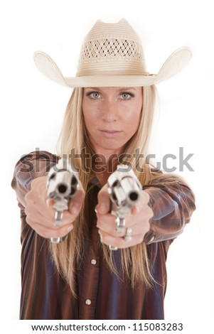 A cowgirl with a serious expression pointing two pistols at the camera. - stock photo