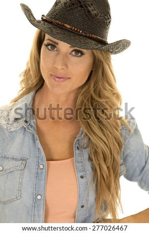 A cowgirl with a small smile and her western hat on her head. - stock photo