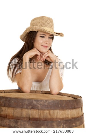 a cowgirl with a small smile on her face hiding behind the barrel. - stock photo