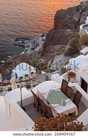 A cozy terrace with chairs and a table. View to the caldera, Santorini, Greece - stock photo