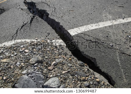 A crack in the pavement, the destruction of the road - stock photo