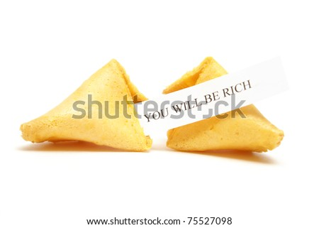 A cracked fortune cookie with the message stating that you will be rich. - stock photo
