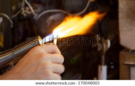 A craftsman glassblower creating pieces of art - stock photo
