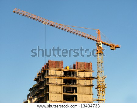 A crane and a building construction on blue sky background - stock photo