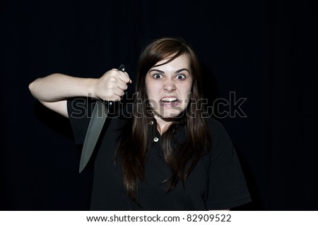 A crazy person with angry expression wielding a knife, on a black background. - stock photo
