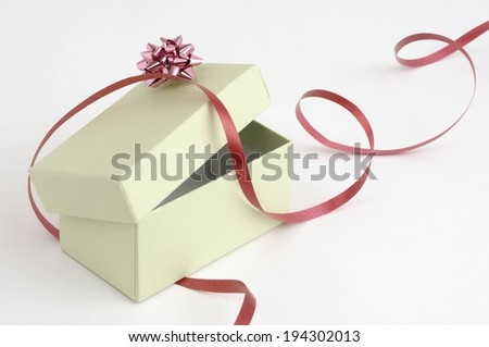A cream colored box partially opened with a red bow and ribbon draped over it. - stock photo