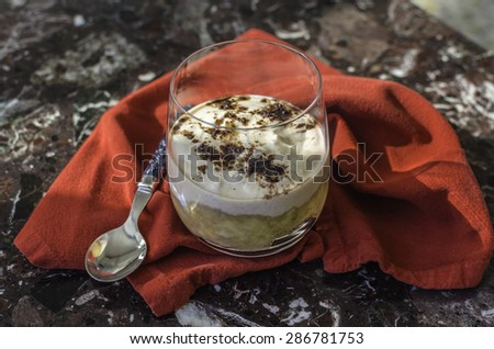 A creamy tiramisu dessert in a glass on a red napkin and marble surface  - stock photo