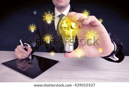 A creative businessman has a bright idea concept with office worker holding light bulb in foreground. - stock photo